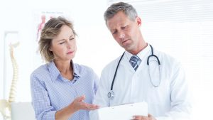 Doctor showing his notes to his patient